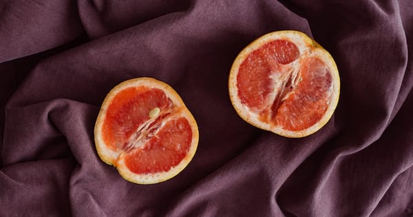 A grapefruit cut in half laying on purple silk