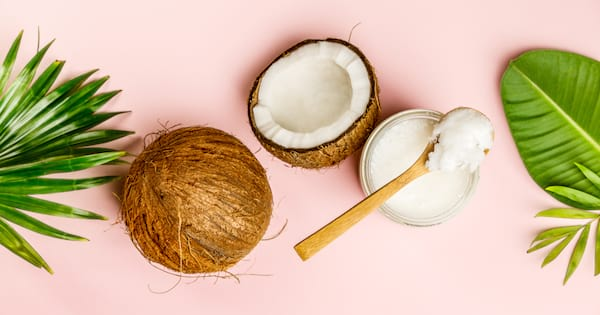 An open coconut sitting next to a jar of coconut oil on a pink background